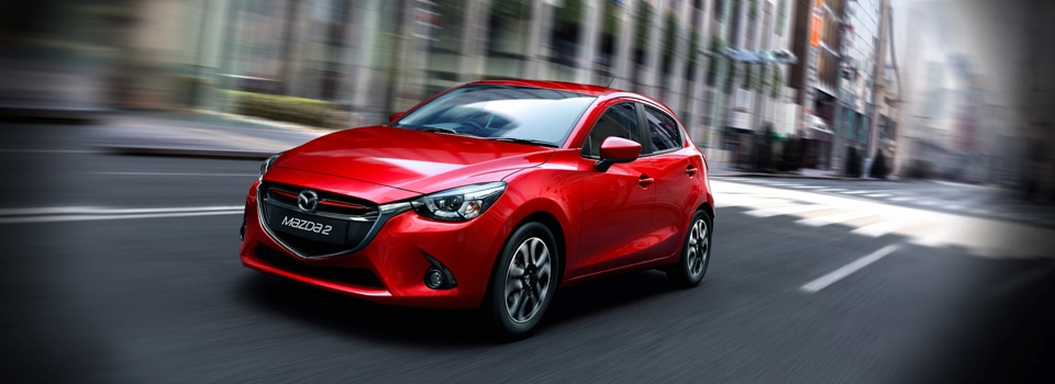Red Mazda 2 driving through street