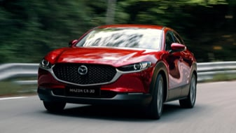 Red Mazda CX-30 driving on an open country road