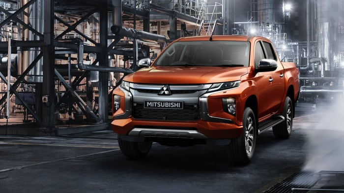 Orange Mitsubishi l200 with industrial background.